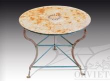 Tavolo in ferro con piano rotondo liscio con rosone centrale a piccoli fori. Base in ferro a tre piedi.