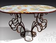 Tavolo con piano decorato con tralci di vite e base in ferro battuto con ampie volute.