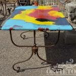 Tavolo con piano in pietra lavica e base in ferro battuto