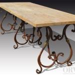 Tavolo con piano in travertino e base a volute in ferro battuto.