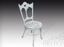 Sedia in ferro con schienale lavorato e seduta decorata da mezzelune forate disposte a rosone.