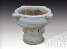 Piccola vasca in marmo decorata con basamento e foro di scarico.